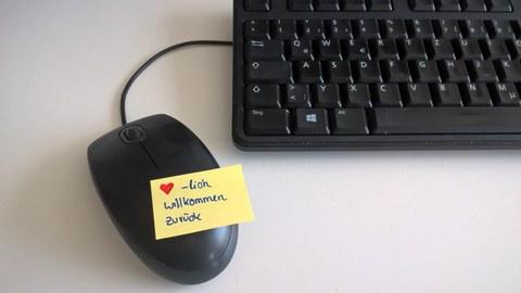 Maus für den Rechner mit einem Postit und dem Schriftzug: Herzlich Wilkommen zurück.