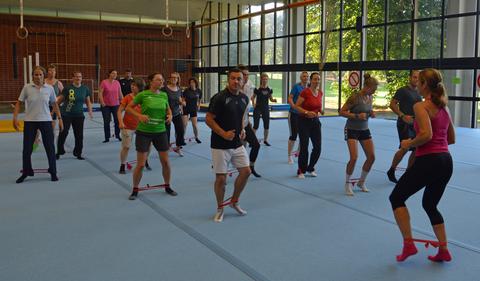 Eine Gruppe von Sportlern trainiert an den Füßen mit dem Terraband.