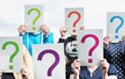 Das Bild zeigt verschiedene Personen, die ein Schild hochhalten, das deren Gesichter verdeckt. Auf dem Schild steht ein Fragezeichen.